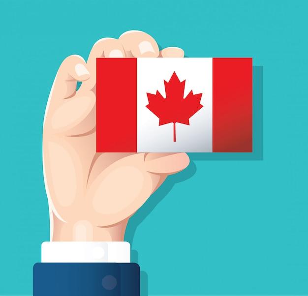 Mão segurando o cartão de bandeira do canadá