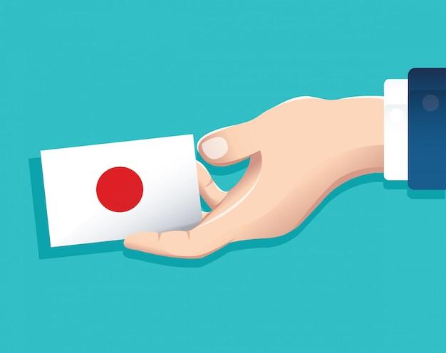 Mão segurando o cartão de bandeira do japão