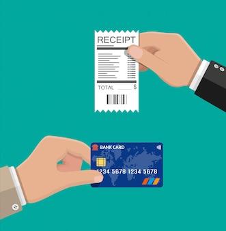 Mão segurando o recibo e cartão de crédito.