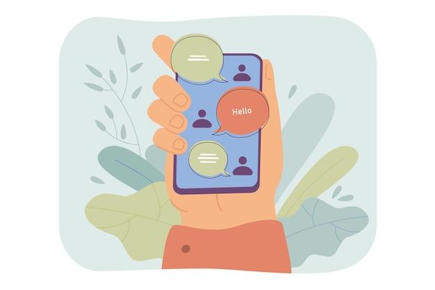 Mão segurando o smartphone com interface de bate-papo online, mensagens enviadas e recebidas na tela