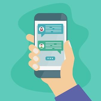 Mão segurando o smartphone com mensagens de texto de bolhas de bate-papo