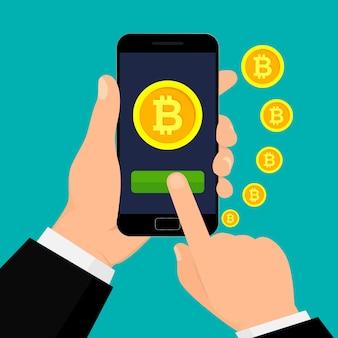 Mão segurando o smartphone com moeda bitcoin.