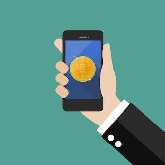 Mão segurando o smartphone com moeda de libra
