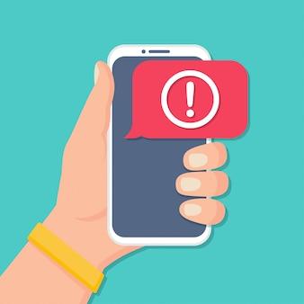 Mão segurando o smartphone com notificação de mensagem de alerta em um design plano