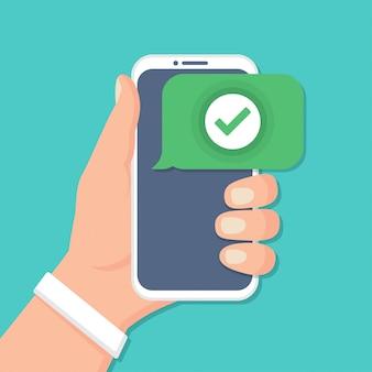 Mão segurando o smartphone com o ícone de seleção em um design plano
