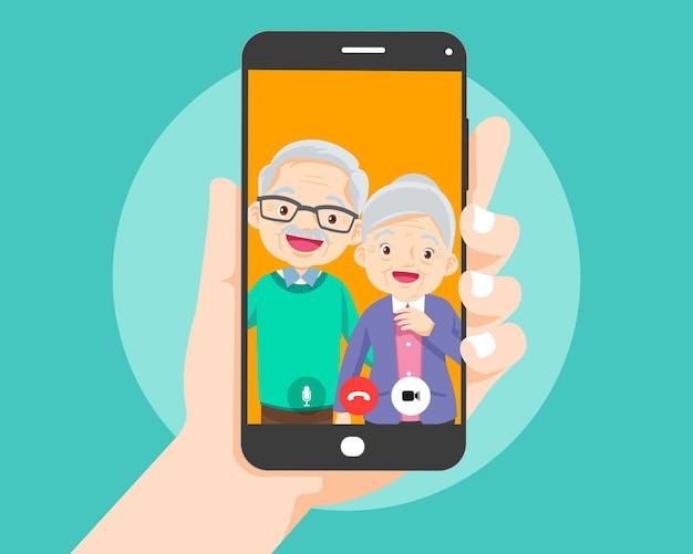 Mão segurando o smartphone com um casal de idosos na tela. videochamada com os avós ou pais idosos.