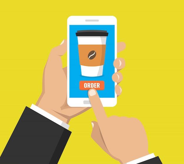 Mão segurando o smartphone com uma xícara de café descartável na tela. pedir comida e bebida conceito