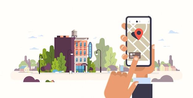 Mão segurando o smartphone conceito de reserva de hotel albergue edifício exterior app móvel gps procurando ponto na paisagem urbana de mapa da cidade