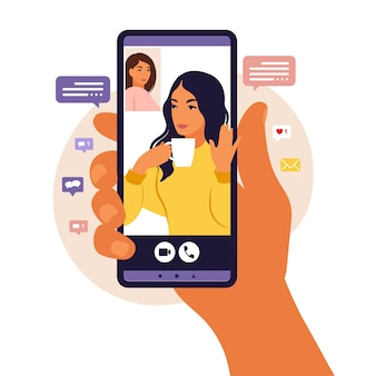 Mão segurando o smartphone conversando com um amigo durante a chamada de vídeo. página de destino. videoconferência com colega, discussão à distância. ilustração. estilo simples.