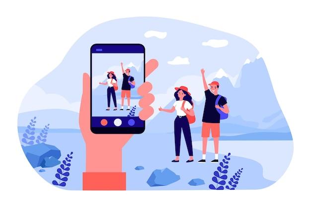 Mão segurando o smartphone, tirando fotos de jovens viajantes. ilustração em vetor plana. homem e mulher posando com mochilas e paisagem montanhosa no fundo. viagem, viagem, foto, conceito de tecnologia