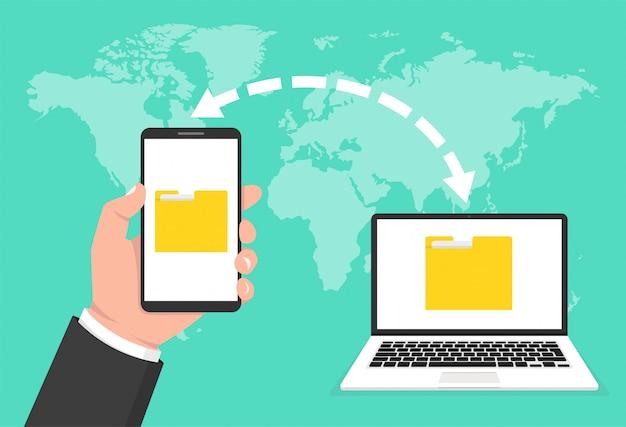 Mão segurando o telefone e documentos transferidos para o laptop