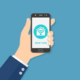 Mão segurando o telefone móvel inteligente com o aplicativo de casa inteligente na tela