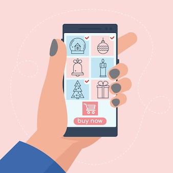 Mão segurando smartphone com imagens de ícones de produtos. compras de natal em smartphone online. ilustração vetorial em estilo simples