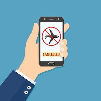 Mão segurando smartphone com informações de voo cancelado
