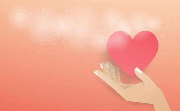 Mão segurando um coração vermelho flutuando fora do envelope com um spray branco sobre o fundo rosa