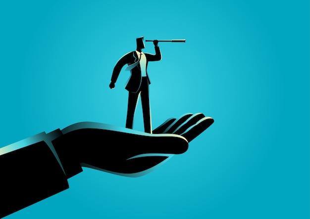 Mão segurando um empresário usando o telescópio