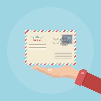 Mão segurando um envelope com ilustração de carimbo de correio