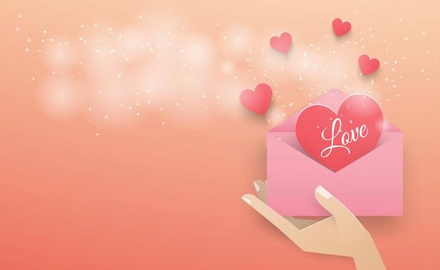 Mão segurando um envelope rosa com um coração vermelho escuro flutuando para fora do envelope com um spray branco sobre o fundo rosa