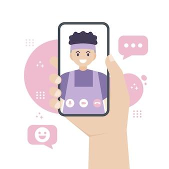 Mão segurando um smartphone enquanto faz uma videochamada para um amigo ou pessoa amada