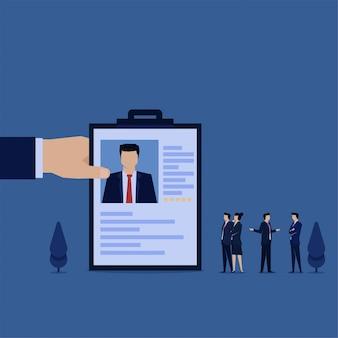 Mão segure cv para novo funcionário e equipe discutem a metáfora da contratação.