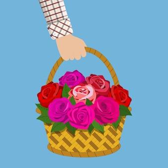 Mão segure o buquê de rosas na cesta.