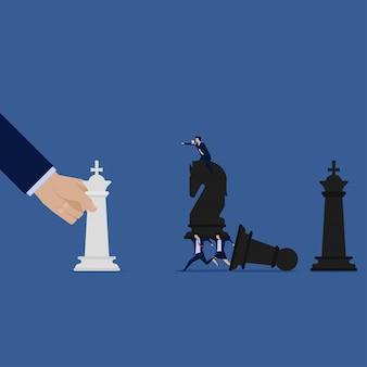 Mão segure o rei enquanto equipe de negócios tem cavaleiro negro.