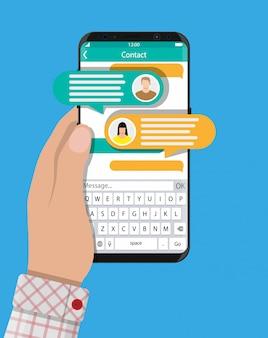 Mão segure o smartphone com o aplicativo de mensagens sms.