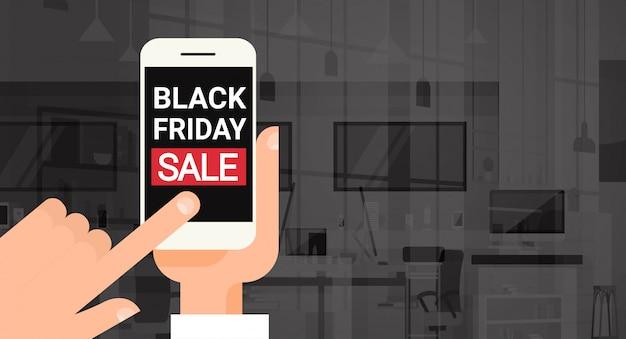 Mão segure o telefone inteligente de celular com preto venda de sexta-feira mensagem desconto banner design