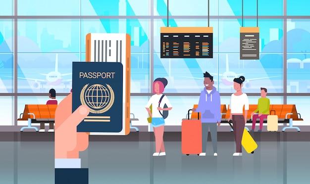 Mão segure passaporte e bilhete sobre pessoas no aeroporto