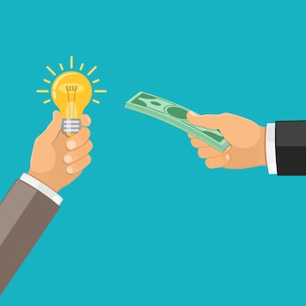Mão trocando dinheiro por lâmpada