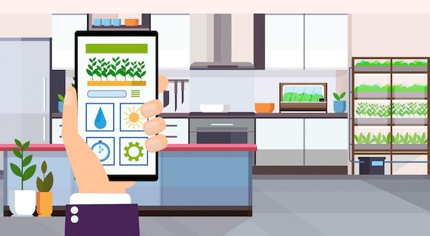 Mão usando controle de casa inteligente aplicação móvel on-line auto plantas rega cuidados conceito moderno casa apartamento cozinha horizontal