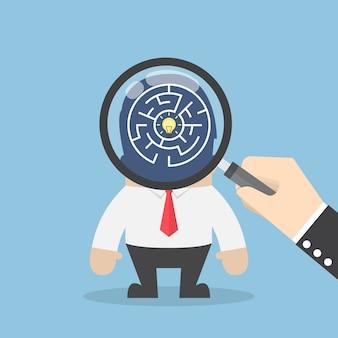 Mão usar lupa para pesquisar a idéia na cabeça do empresário