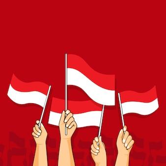 Mãos agitando bandeiras indonésia