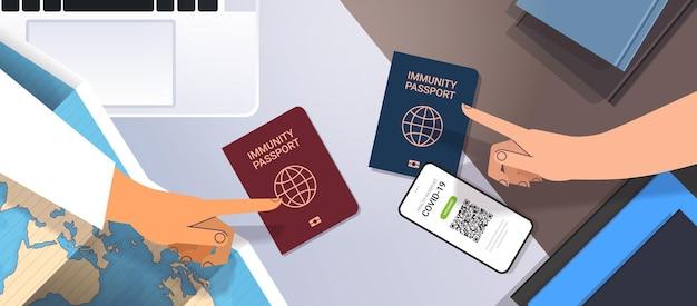 Mãos apontando para passaportes de imunidade global sem risco de reinfecção covid-19 certificado pcr conceito de imunidade de coronavírus local de trabalho mesa vista de cima ângulo ilustração vetorial horizontal