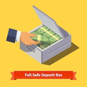 Mãos colocando pilha de dinheiro para um cofre
