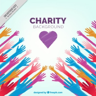 Mãos coloridas e um fundo do coração a caridade
