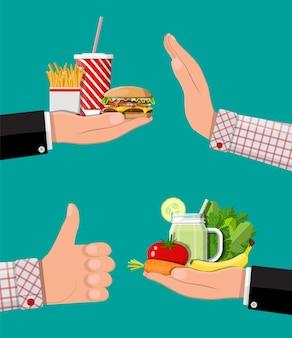 Mãos com fast food e produtos orgânicos. dieta, nutrição, fitness e perda de peso ou excesso de peso e gordura. colesterol gorduroso vs. vitaminas de frutas vegetais.