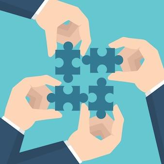 Mãos de empresário segurando um quebra-cabeça. conceito de trabalho em equipe.