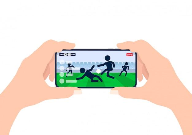 Mãos de homem segurando um smartphone e assistir qualquer jogo de futebol ao vivo on-line.