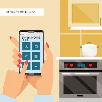 Mãos de mulher segurando um smartphone com app para casa inteligente na tela. internet das coisas para cozinha. panela no fogão.