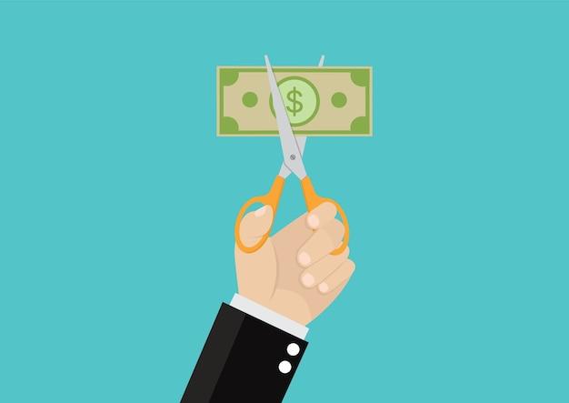 Mãos do homem de negócios que guardam as tesouras que cortam a conta de dinheiro.