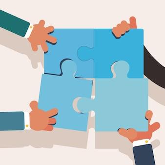 Mãos do trabalho em equipe, criando um quebra-cabeça perfeito