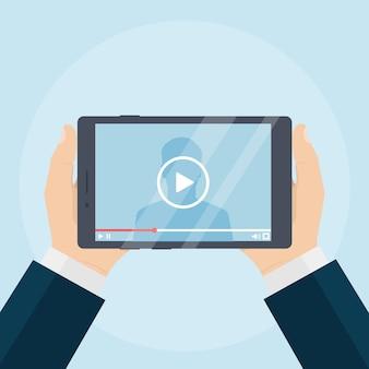 Mãos humanas segurando um tablet com reprodutor de vídeo na tela