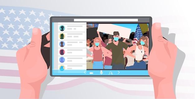 Mãos humanas usando o tablet pc assistindo vídeo on-line pessoas com máscaras segurando bandeiras dos eua comemoração do dia do trabalho coronavírus retrato do conceito de quarentena