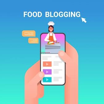 Mãos humanas usando smartphone com comida blogger na tela