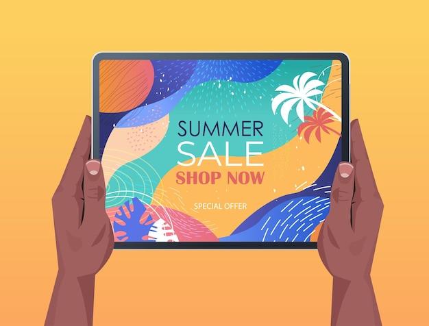 Mãos humanas usando tablet pc com panfleto de banner de venda de verão ou cartão na tela