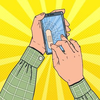 Mãos masculinas segurando um smartphone quebrado