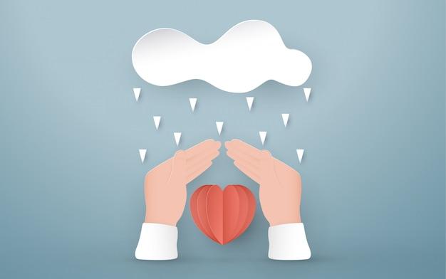 Mãos protegem o coração vermelho.