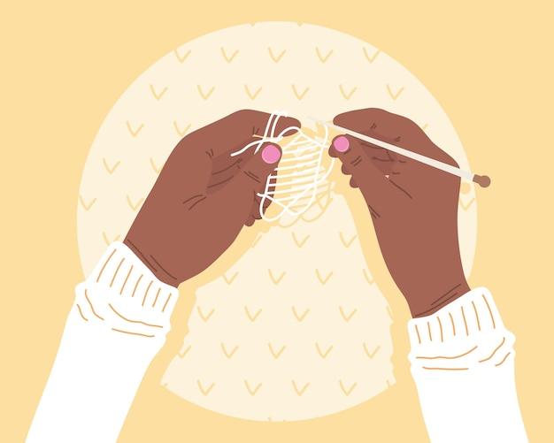 Mãos segurando agulha de tricô