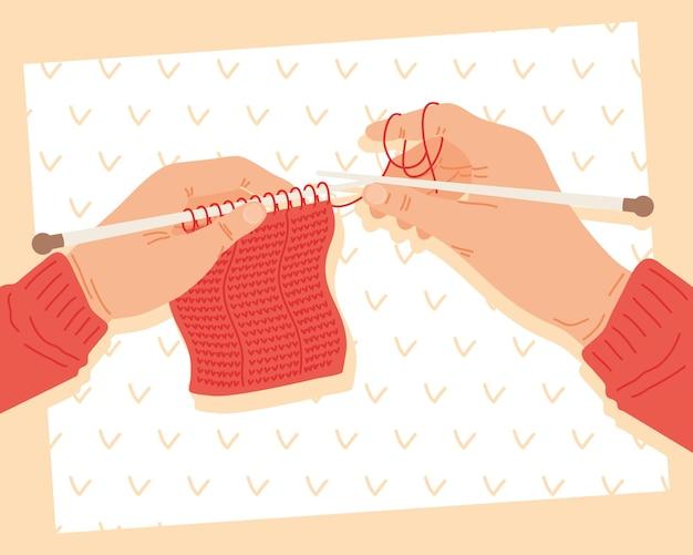 Mãos segurando agulhas de tricô com padrão